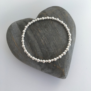 This stretch bracelet is made with super shiny, round, Sterling silver beads. The beads are small, approximately 3mm and 4mm in size.