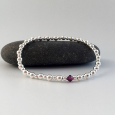 Sterling silver birthstone bracelet featuring Swarovski crystal elements. This stretch bracelet is made with 3mm and 4mm shiny Sterling silver beads and features a birthstone Swarovski crystal element, this is the February version.