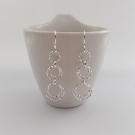 Long, dangly Sterling silver circle earrings with five sparkly, diamond cut, Sterling silver rings.