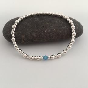 Sterling silver stretch bracelet with Aquamarine Swarovski crystal element.