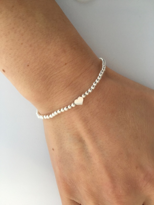 This stretch bracelet is made with super shiny, round, Sterling silver beads. The beads are small, approximately 3mm. The heart charm is also very small (about 5x6mm).