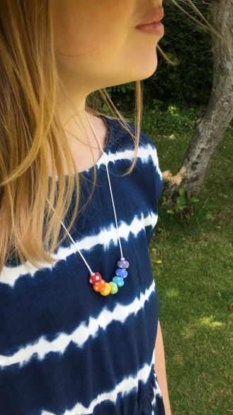 Rainbow necklace made with matte, polka dot, lampwork glass beads and Sterling silver spacers on soft, white cotton cord.