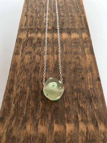 Beautiful lime green lampwork bead with white, blue and black spots on Sterling silver chain.